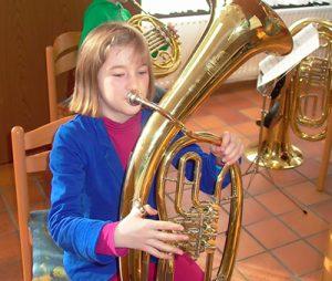 Kind bekommt ersten Unterricht auf der Tuba