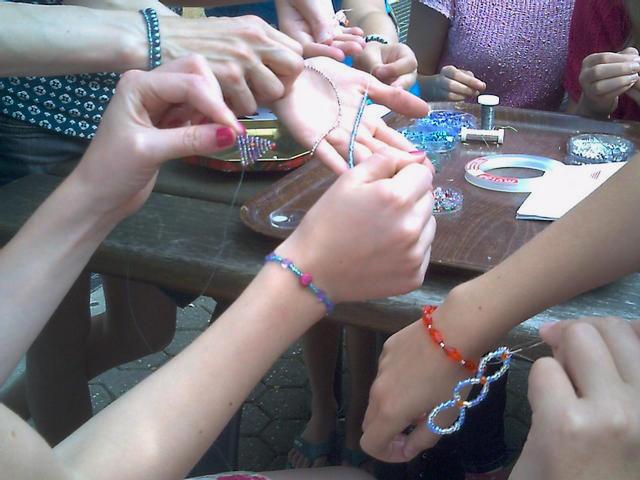 Teilnehmer basteln Armbänder