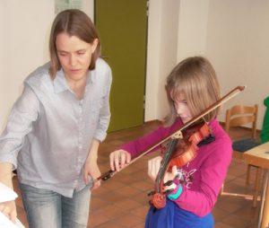Kinder lernen die ersten Grundlagen auf der Geige.